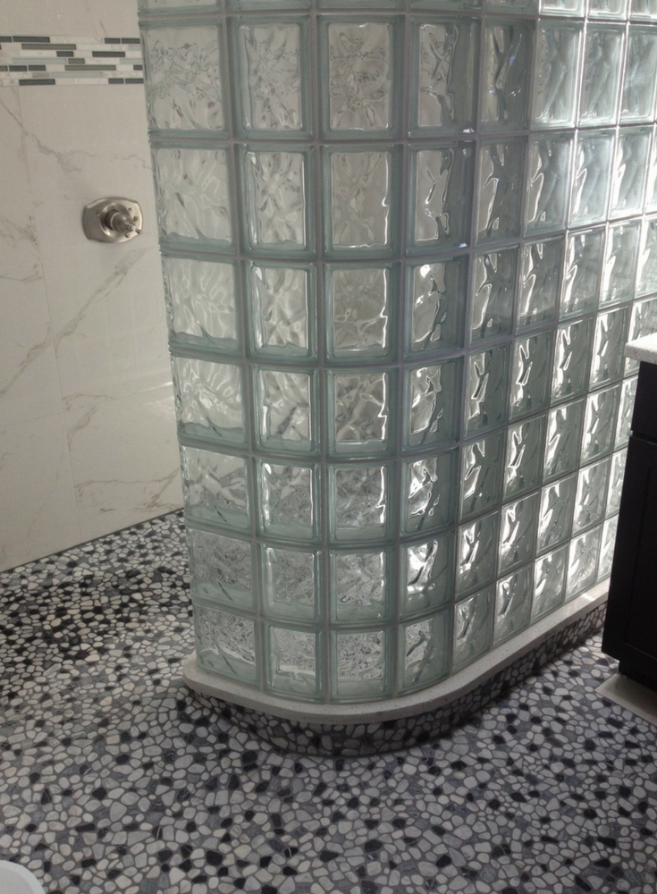 Curved glass block shower wall set on a ready for tile shower pan with a barrier free entry. | Innovate Building Solutions #GlassBlock #GlassBlockShower #ShowerRemodeling