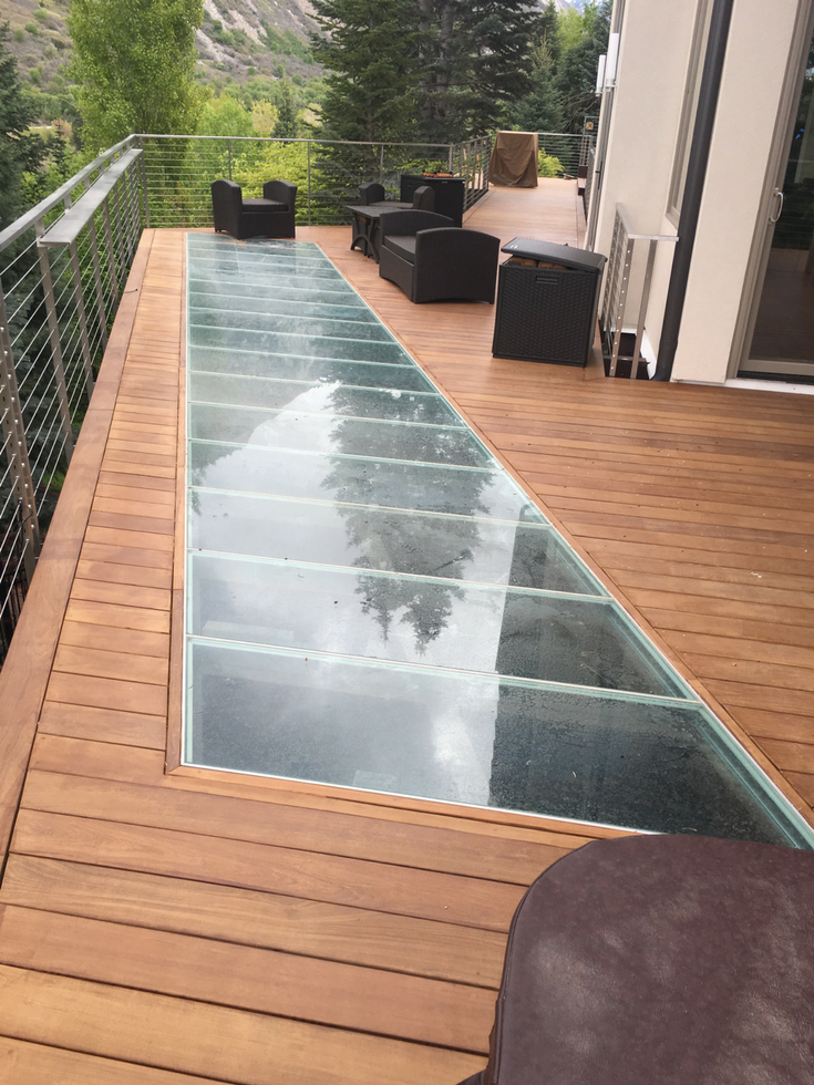 Glass decking to move light to a patio level below | Innovate Building Solutions