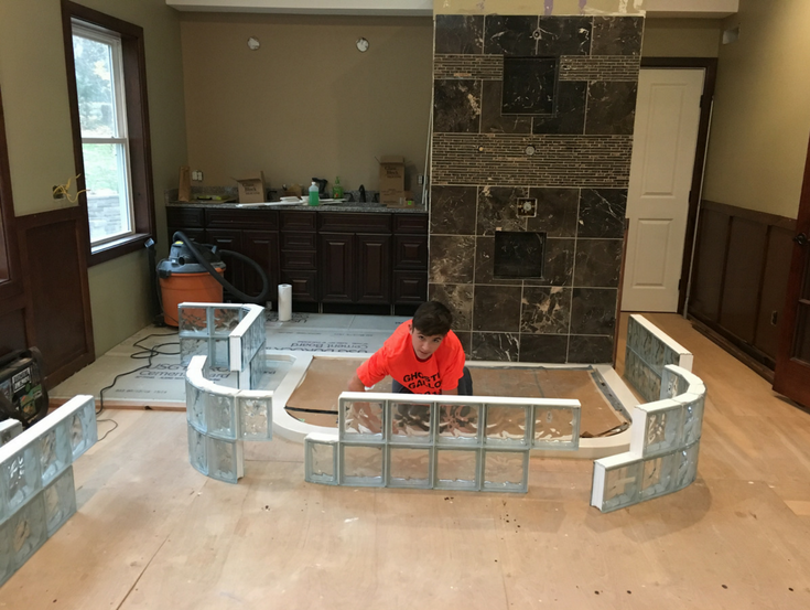 Glass block wall sections staged to go on a cultured stone base | Innovate Building Solutions | #GlassBlockWall #GlassBlockDesign #ColorGlassBlock