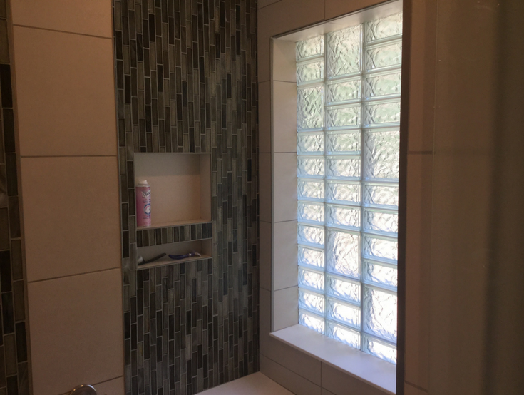 Niche storage around a multi size glass block bathroom window | Innovate Building Solutions | #BathroomStorage #GlassBlock #ShowerDesign