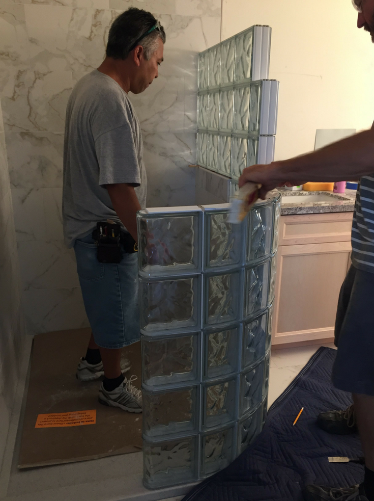 Prefabricated glass block shower wall panels being installed | Innovate Building Solutions | #GlassBlockShower #GlassBlockInstallation #CurvedGlassBlock