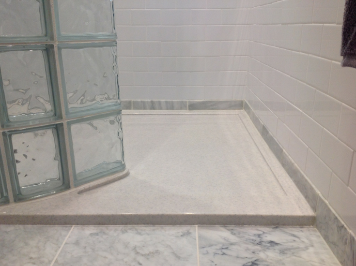 SCultured stone low profile shower pan with a curved glass block wall | Innovate Building Solutions