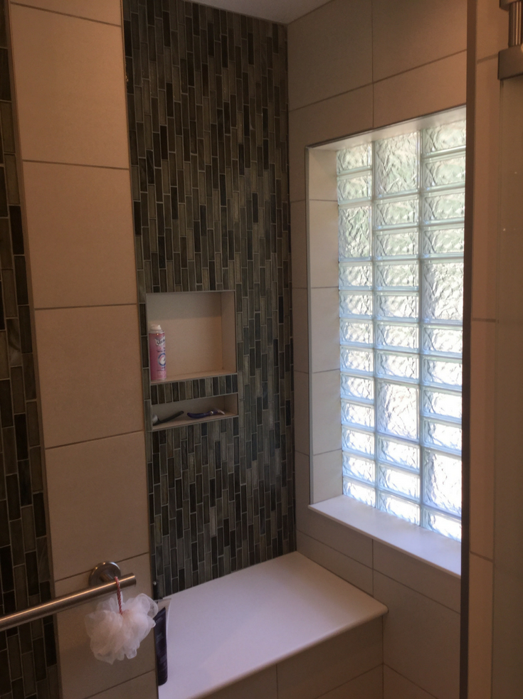 Niche in a shower with a glass block bathroom window with a multi block | Innovate Building Solutions | #GlassBlockWindow #BathroomWindow #NicheBathroom #ShowerStorage