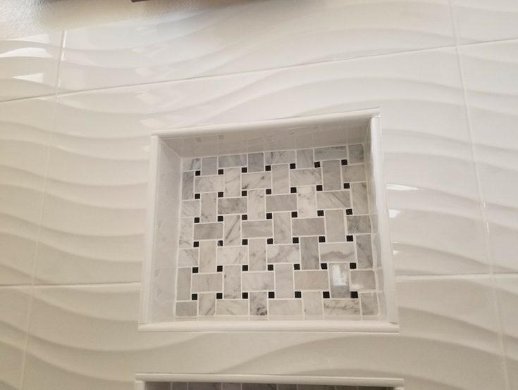 White ceramic wave pattern 3 dimensional tiles in a walk in shower | Innovate Building Solutions | #ShowerPanels #WalkInShower #CeramicTiles