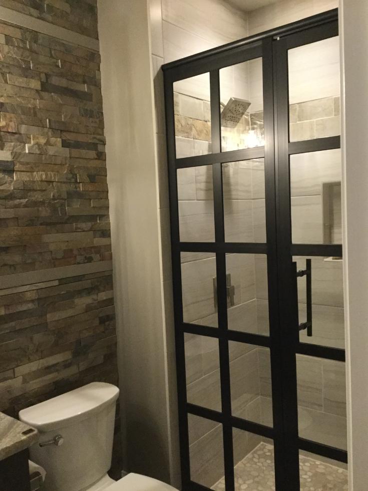 Black framed shower doors in an organic bathroom | Innovate Building Solutions | #ShowerDoors #BathroomTrends #StylishBathroom
