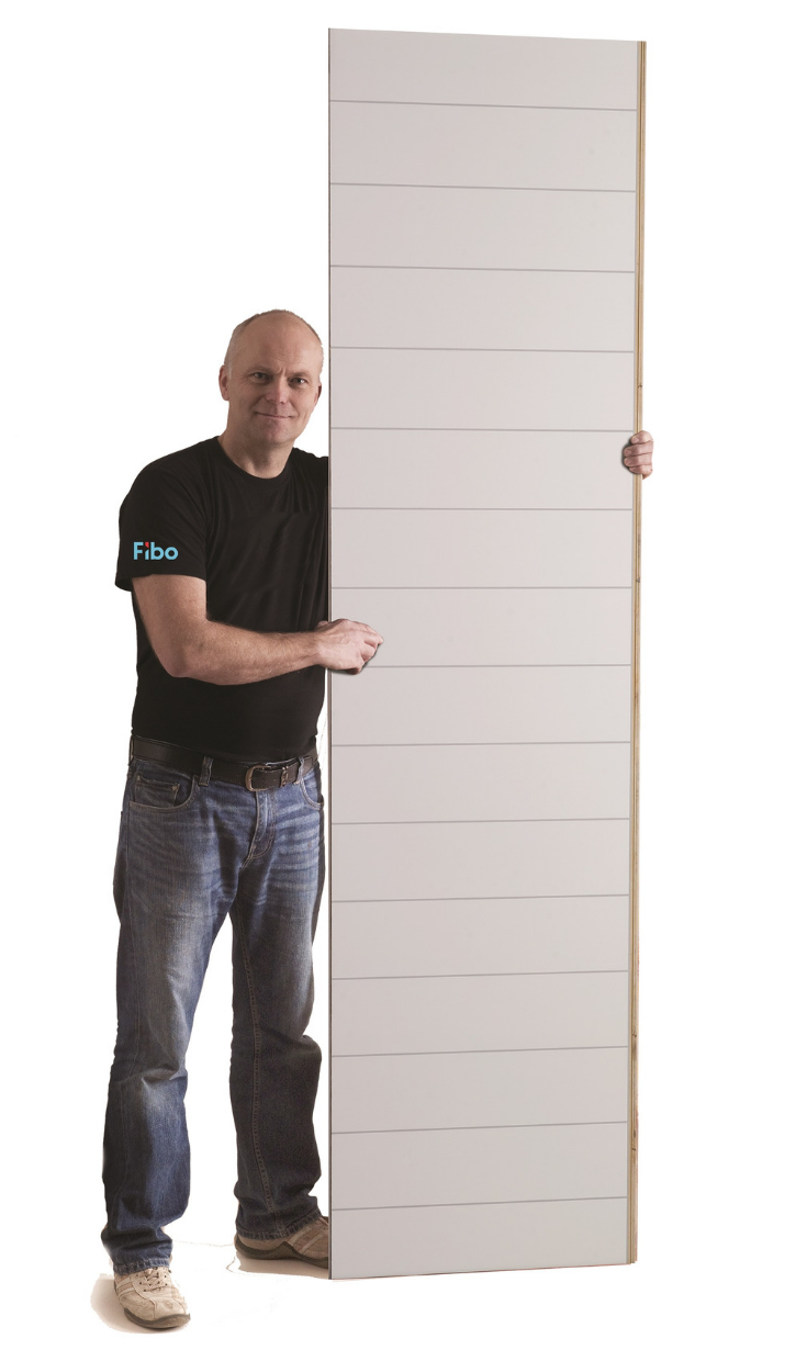 Guy holding up 2 foot by 8 foot laminated wall panel | Innovate Building Solutions | #LaminatePanels #ShowerWallPanels #DIYShowerPanels