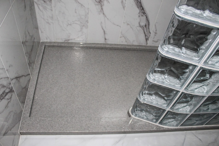 Glass block shower wall around a solid surface shower pan | Innovate Building Solutions | #GlassBlockShower #GlassBlockDesign #ShowerBase #SolidSurfaceBase