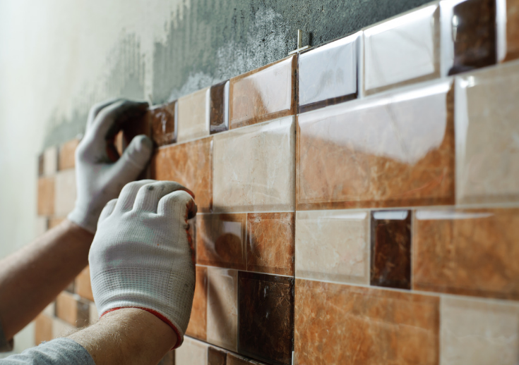 person installing tile | Innovate Building Solutions | #installingtile #tile #grouttile