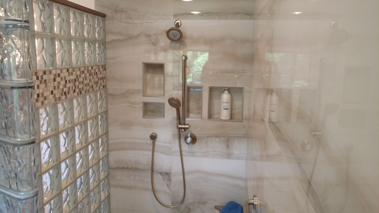 Glass block shower kit with a tile border row | Innovate Building Solutions | #LargeTile #GlassBlockShower #bathroomremodeling