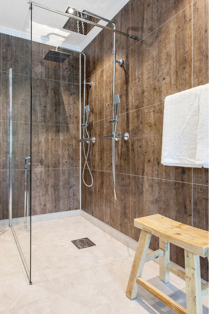Laminated shower wall panels in a rough wood design | Innovate Building Solutions | #LaminateWallPanels #ShowerWallPanels #ShowerRemodel