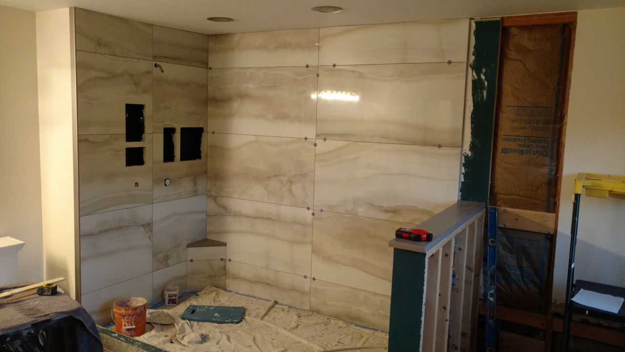 Large format 2 foot x 4 foot tiles during installation | Innovate Building Solutions | #BathroomRemodeling #TileShower #TileBase #LargeFormatTiles
