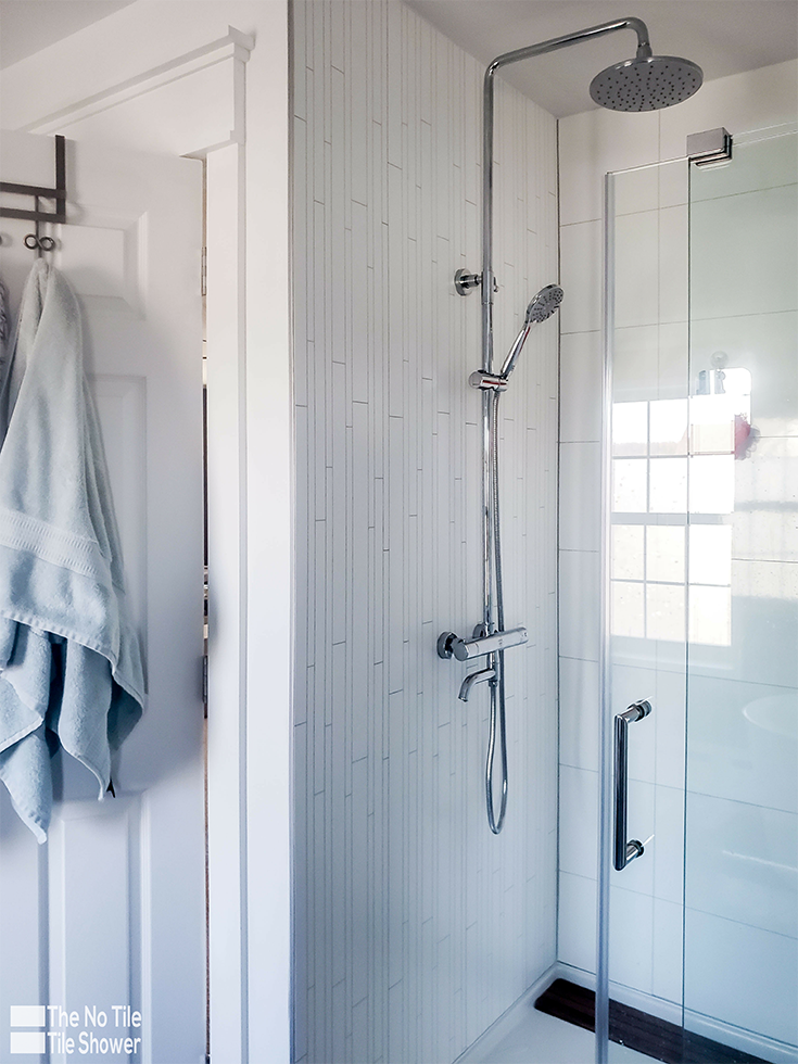 A rain head in with laminated DIY shower wall panels | Innovate Building Solutions | #LaminatePanels #DIYShowerRemodel #ShowerInstall #ShowerHead