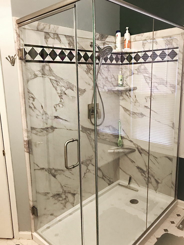 PVC composite shower panels in a calcutta white pattern | Innovate Building Solutions | #PVCShower #ShowerPan #BathroomRemodel