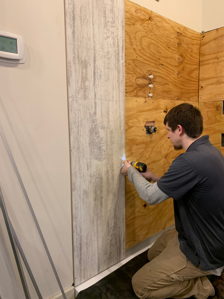 Fibo laminate shower panels screwed onto OSB by one person | Innovate Building Solutions | #OSBBoard #WallPanels #Laminatewallpanels #Easyinstall #DIYShowerinstall