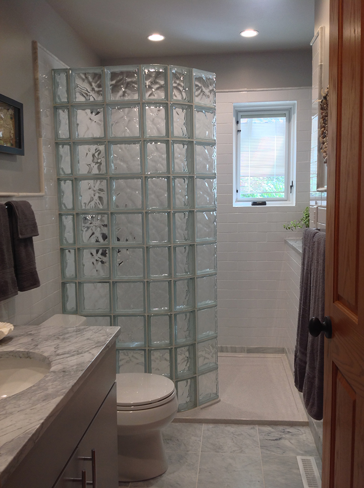 Tub to shower conversion with a curved glass block wall and a solid surface base | Innovate building solutions