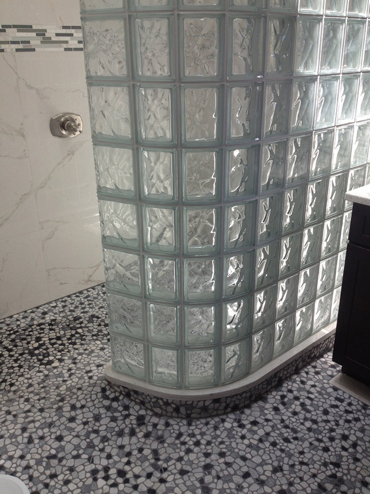 glass block wall with a mosaic tile shower pan floor which is hard to maintain | Innovate Building Solutions | #GlassBlockShower #TileShower #GlasaBlockShower