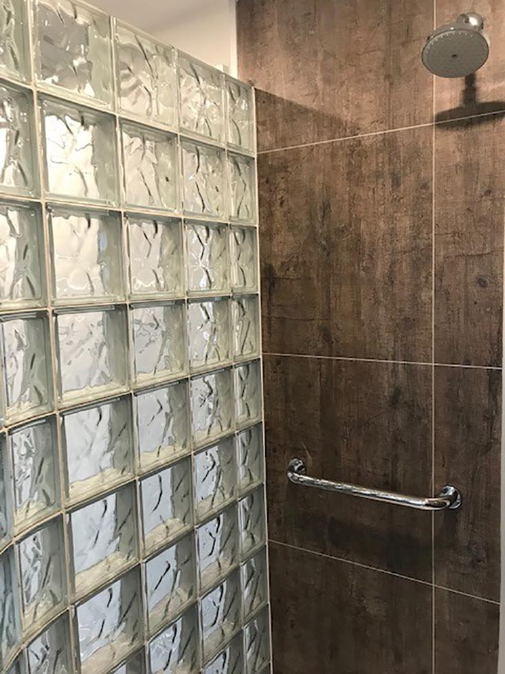 rough wood manly laminate grout free shower wall panel system glass block wall | Innovate Building Solutions | #WallPanels #ShowerWallPanels #LaminateWallPanel #RoughWood
