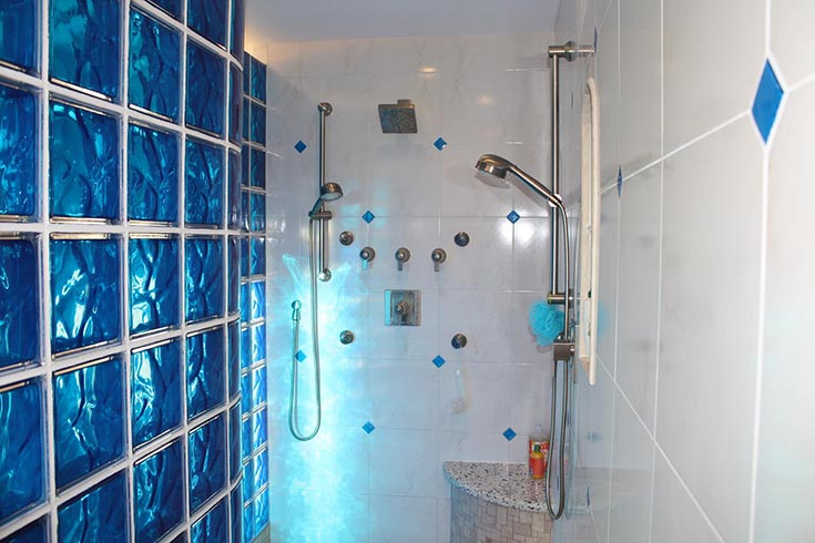 light shining through a colored glass block wall | Innovate Building Solutions | #Glassblockshower #Glassblockdesign #BathroomLight