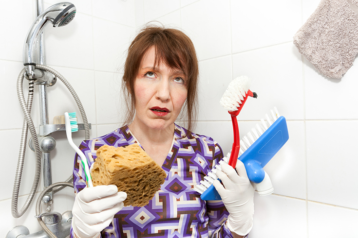 woman with scrub brushes hating tile shower | Innovate Building Solutions | #BathroomRemodel #CleaningGrout #ScrubbingTile