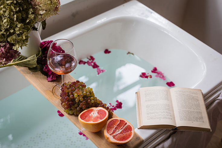 Bath tub with a tray with grapefruit slices, bunch of grapes, a glass of wine and a book | Innovate Building Solutions | #Bathtube #ShowerTub #SpaDay #BathroomSpa