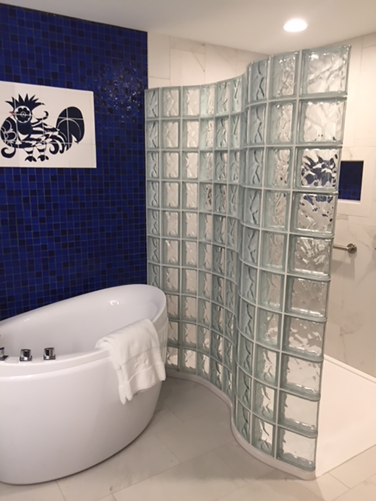 Tip 7 serpentine shaped custom cultured granite shower pan with a glass block wall | Innovate Building Solutions #GlassBlock #ShowerWall #GlassShower