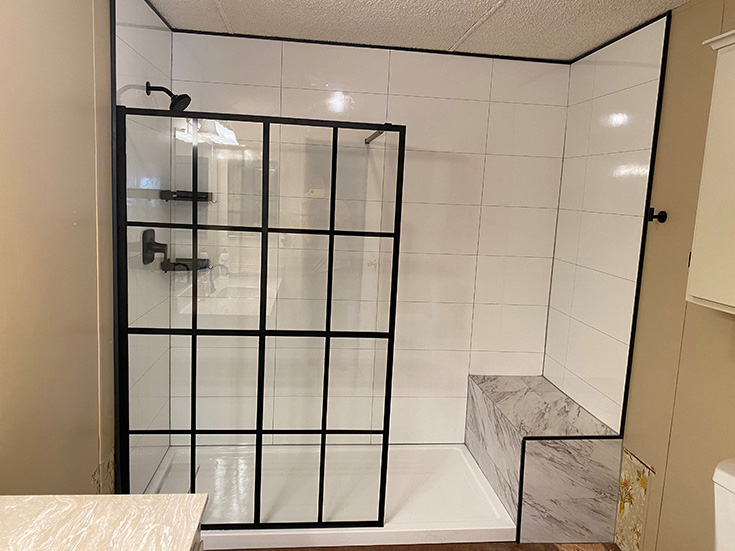 Question 7 matte black fixed shower door with white marble laminate shower panels and a bench seat | Innovate Building Solutions #showerdoor #laminatewallpanels #Whiteshower